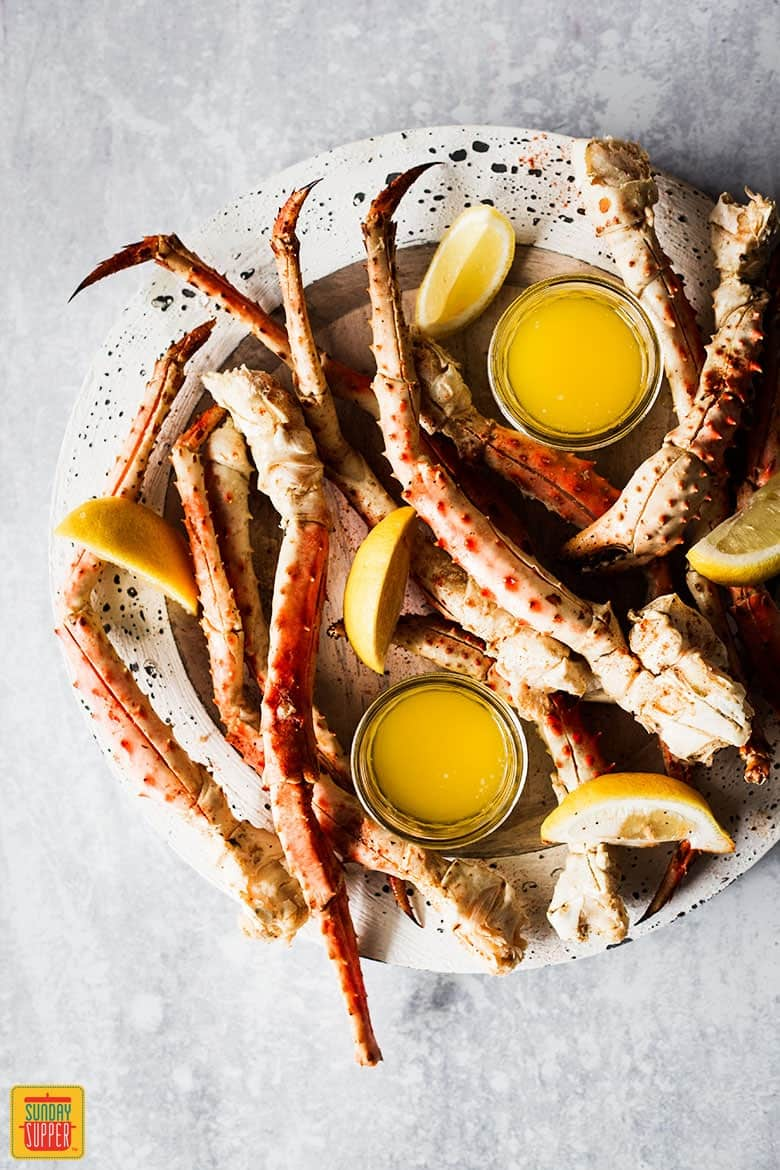 Steamed Crab Legs Recipe - king crab legs on speckled white plate with garlic butter dipping sauce and lemon slices