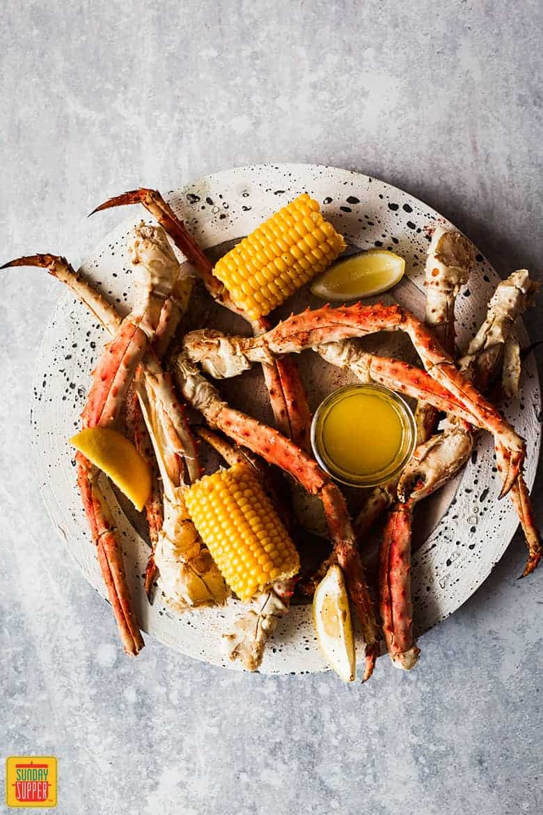Steamed crab legs on a plate with butter, corn and lemon