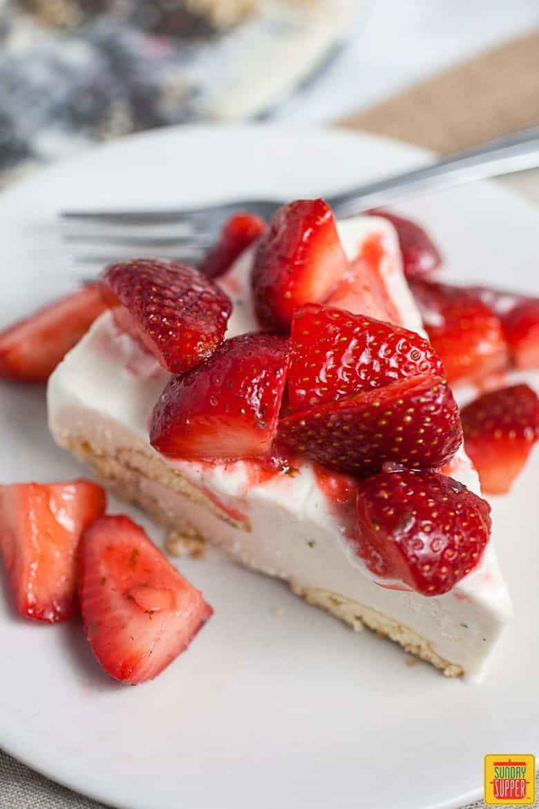 Slice of Carlota de Limon  on a white plate with a fork and fresh strawberries on toptopped with fresh strawberries
