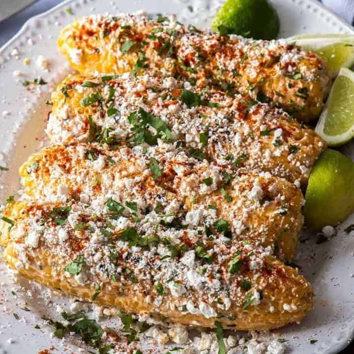 Four grilled corn, topped with cheese on a white plate.