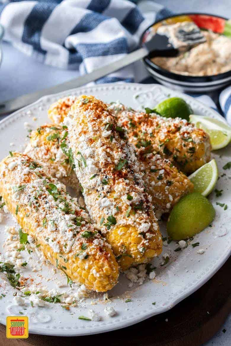 Four Elotes on a white plate