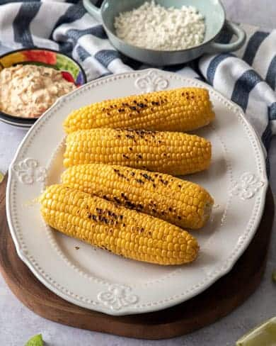 Four grilled corn cobs on a white platter
