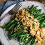 Green beans almondine on a grey speckled plate with a fork