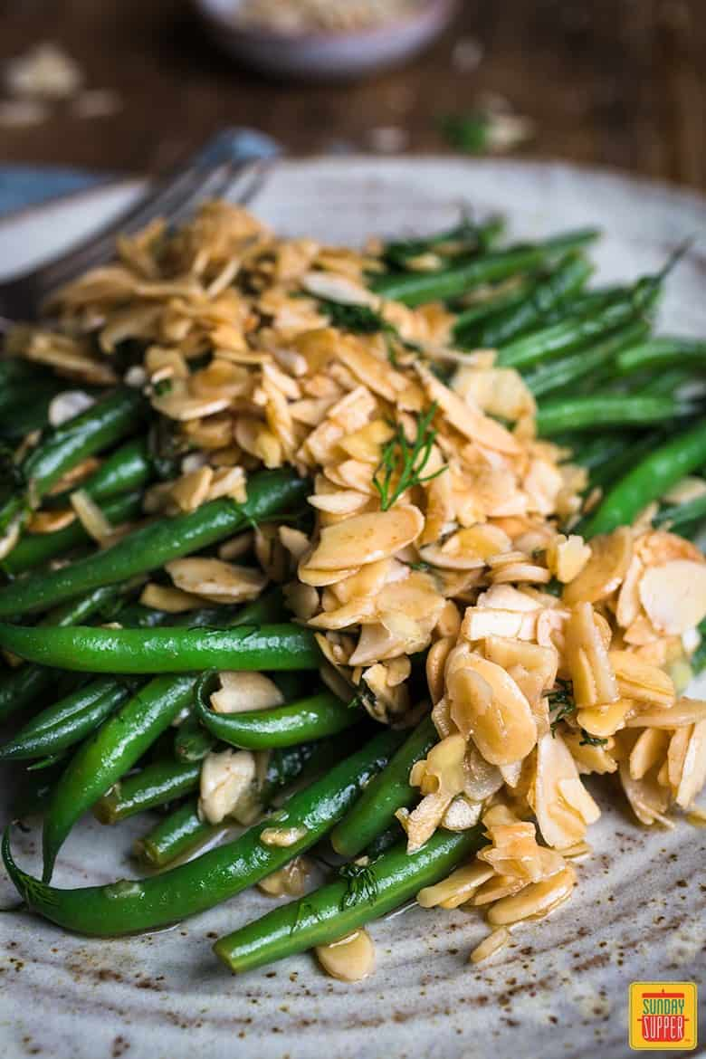green beans pan fried with butter and flaked almonds on a speckled plate