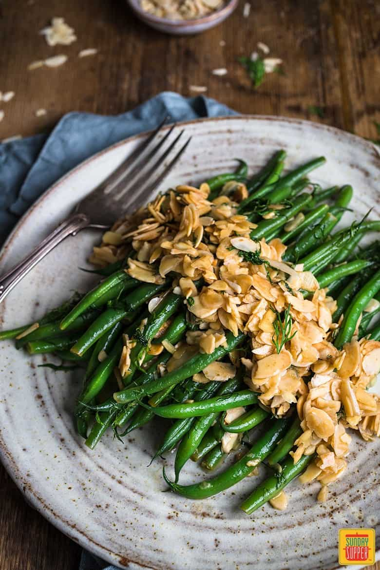 green beans served with almonds in butter on a gray plate with a fork