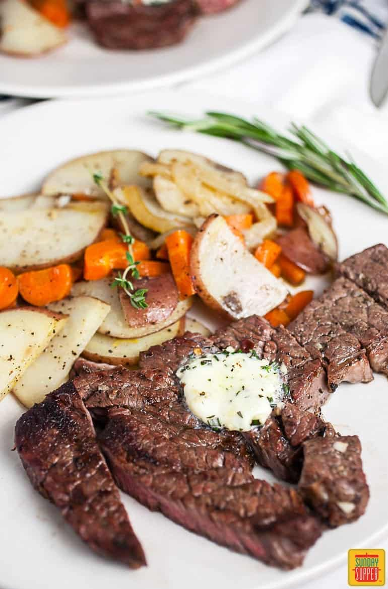 Sliced grilled chuck steak with compound butter on top on a white plate next to potatoes and carrots and fresh rosemary