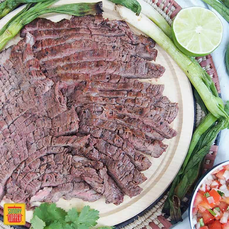 Carne Asada thinly sliced on a wooden plate with grilled green onions, half a lime and pico de gallo in a little bowl