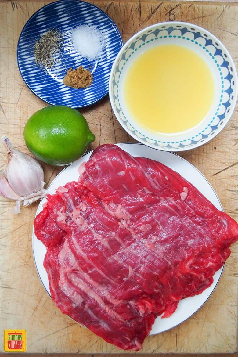 Ingredients for carne asada recipe set out on cutting board: steak, lime, garlic, orange juice, and spices