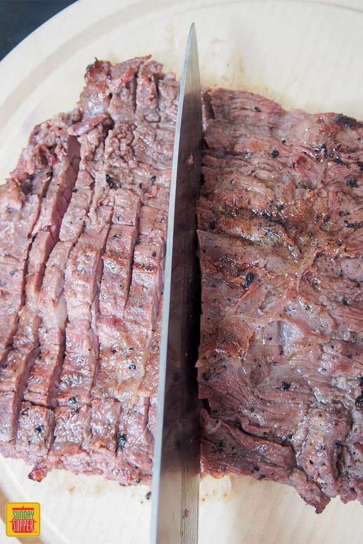 Slicing steak across the grain for authentic carne asada reecipe