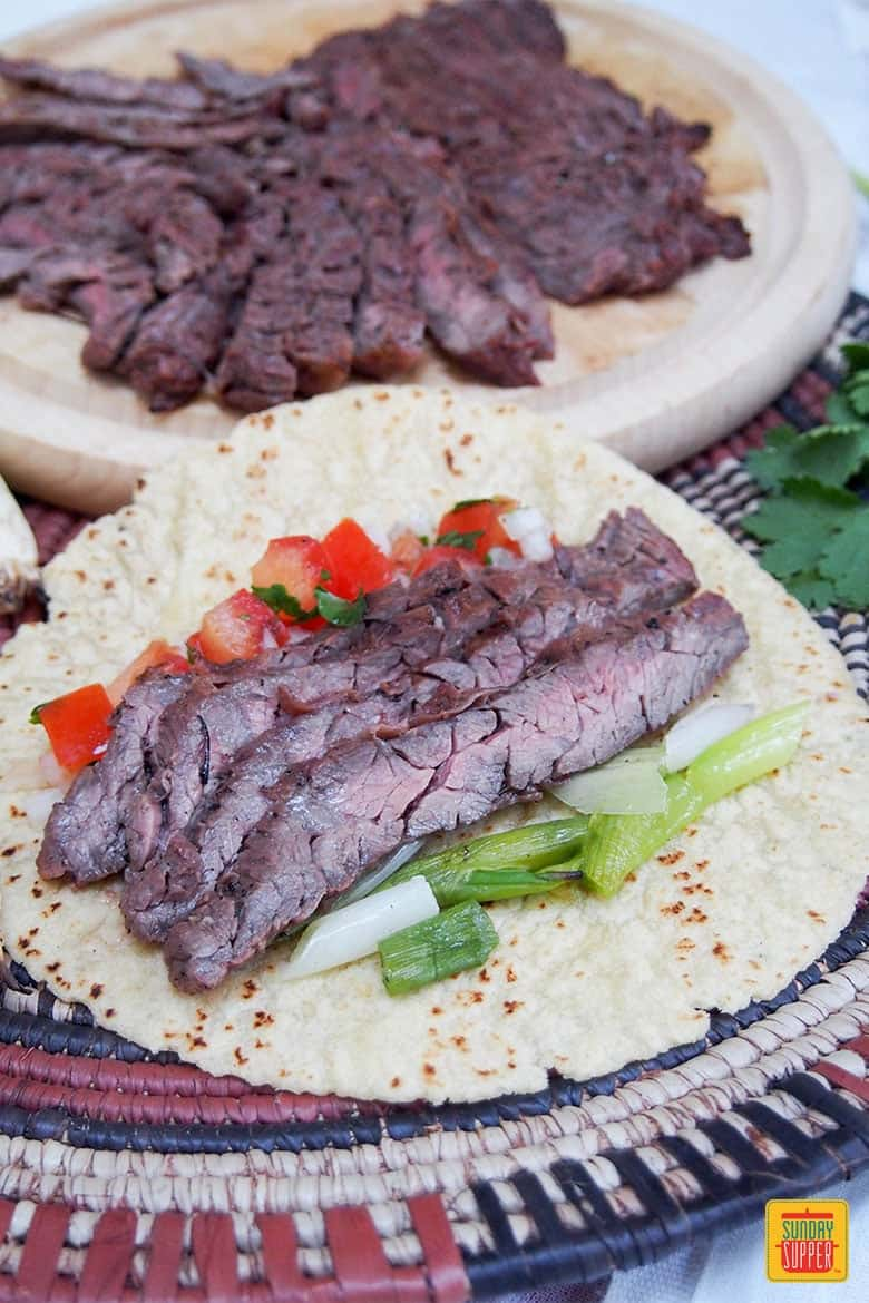 Slices of beef with pico de gallo and grilled green onion in a taco shell for carne asada tacos