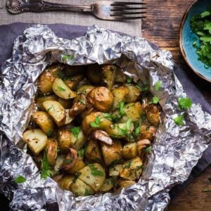 Potatoes in foil with garlic and herbs on a wooden surface