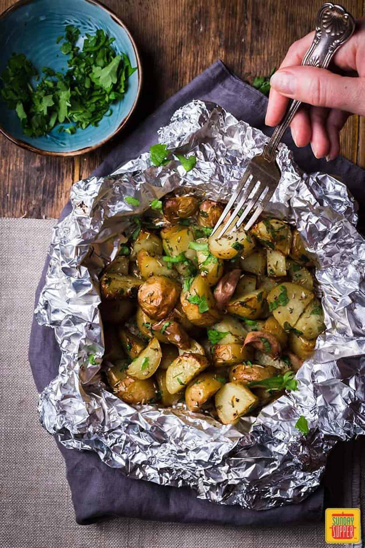 Holding a fork through the foil pack potatoes on a wooden table