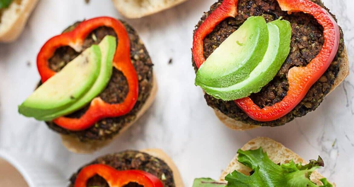 How To Make Veggie Burgers: Black bean burgers on ciabatta buns with fresh avocado and red bell pepper slices ready to eat