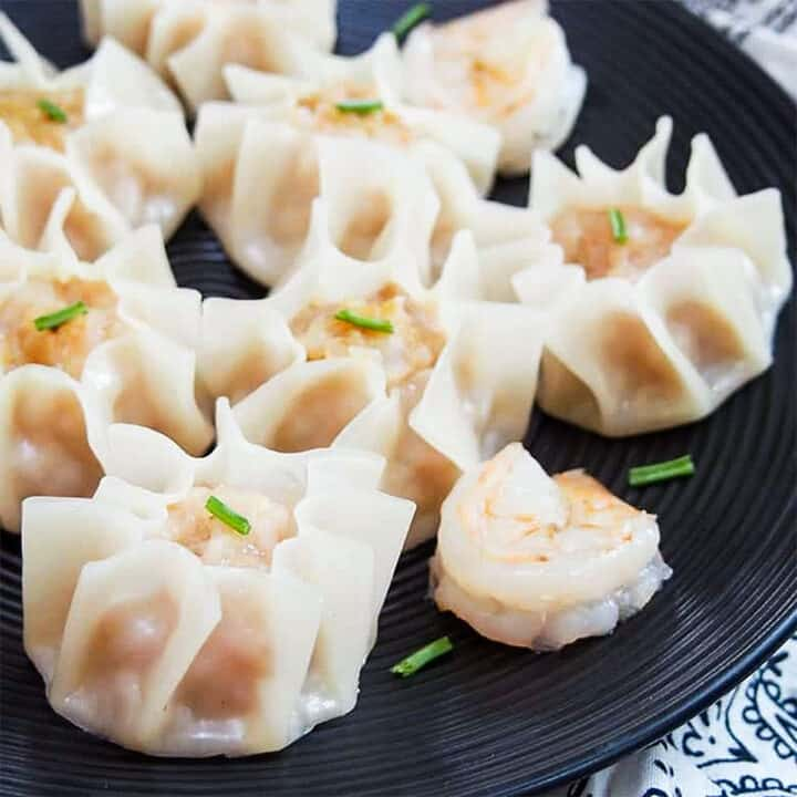 Shrimp shumai recipe on a black plate with a cooked shrimp on the plate