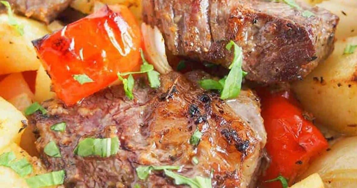 Close up of steak foil packs with potatoes, peppers, and onions, cooked and ready to eat