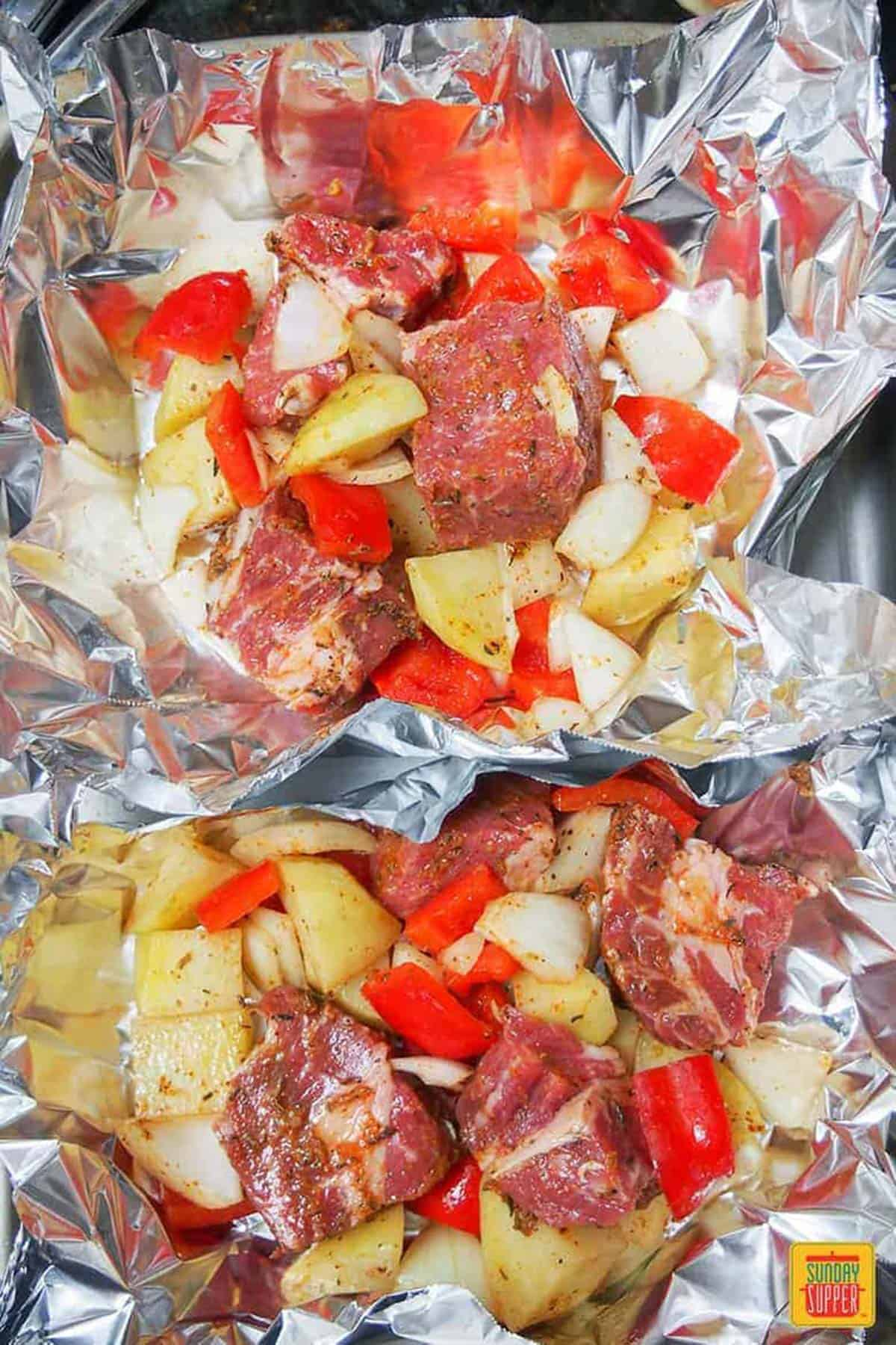 Steak, onions, peppers, and seasonings with potatoes in a foil pack