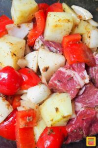 Chopped peppers, steak, onions, and potatoes coated with oil and seasonings, close up