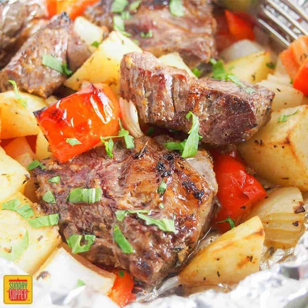 Close up of steak foil packets with peppers and onions and potatoes
