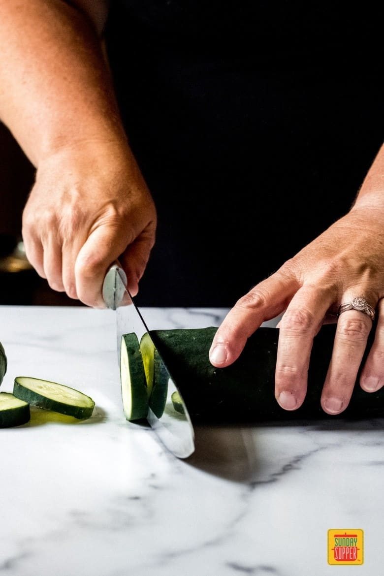 a woman slicing a cucumber with a knife