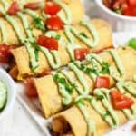 Chicken taquitos recipe with avocado crema on white platter