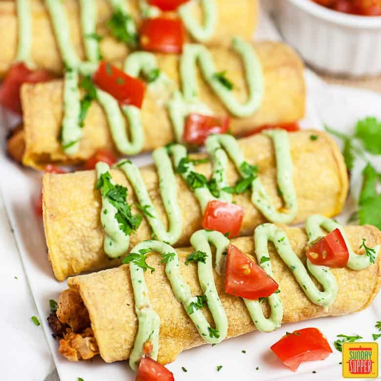 Chicken taquitos all in a row with fresh crema on top