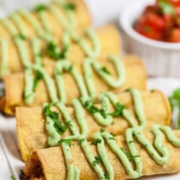 Chicken Taquitos Recipe: chicken taquitos on white platter with fresh avocado crema