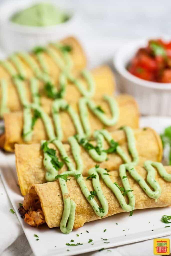 chicken taquitos recipe on a white platter with fresh avocado crema