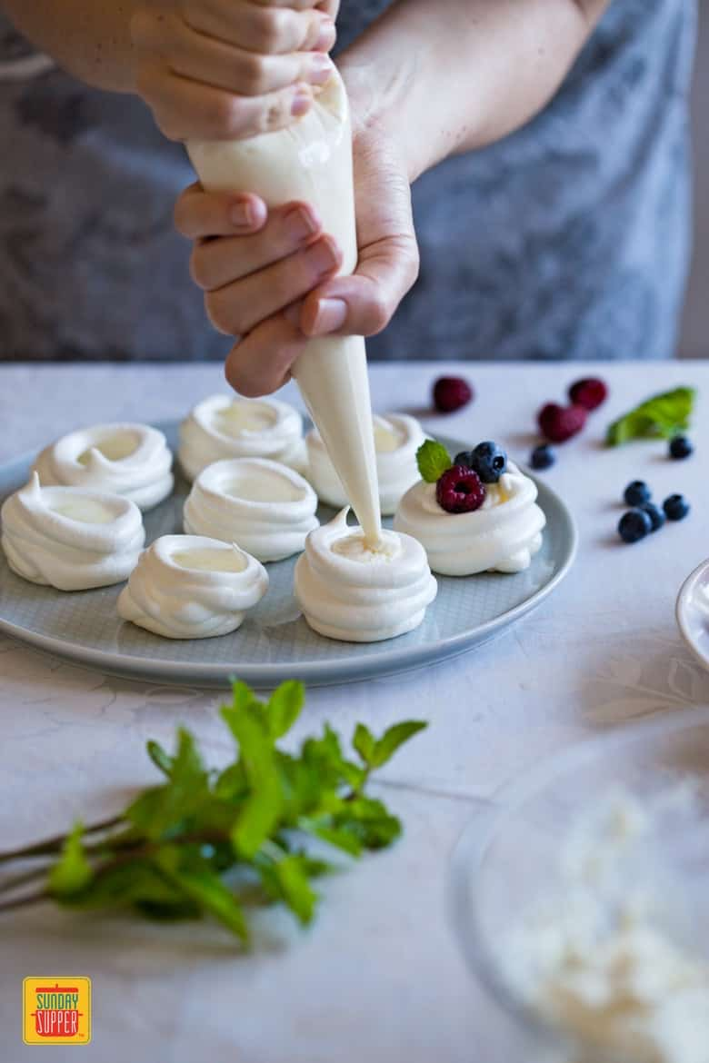 Filling the mini pavlovas with mascarpone and whipped cream filling with piping bag