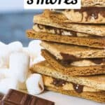 air fryer s'mores pin image - s'mores stacked on top of each other next to chocolate and marshmallows