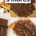 air fryer s'mores pin image - lifting one graham cracker to show the chocolate inside