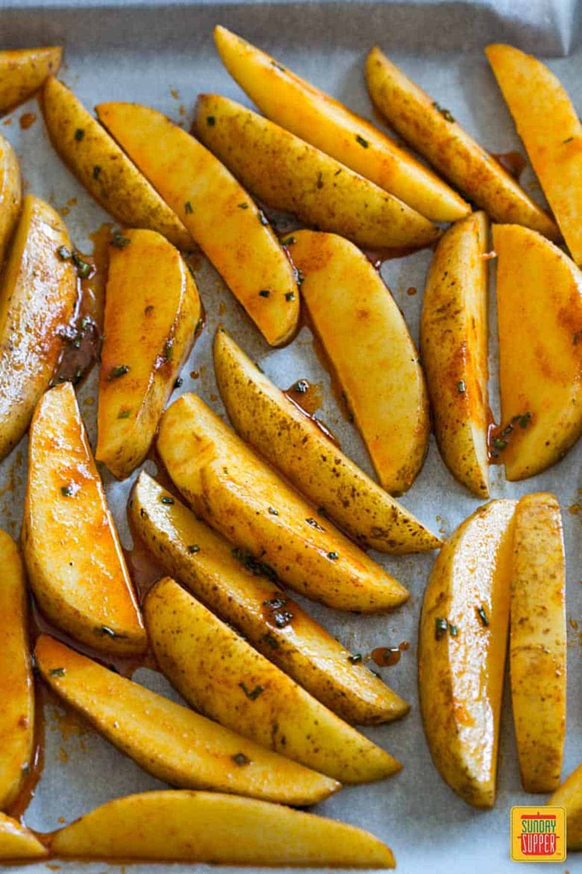 Unbaked potato wedges on a baking sheet