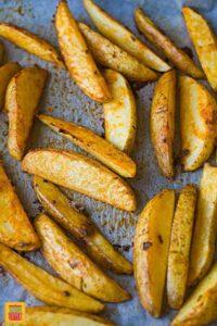 Baked crispy potato wedges on a baking sheet
