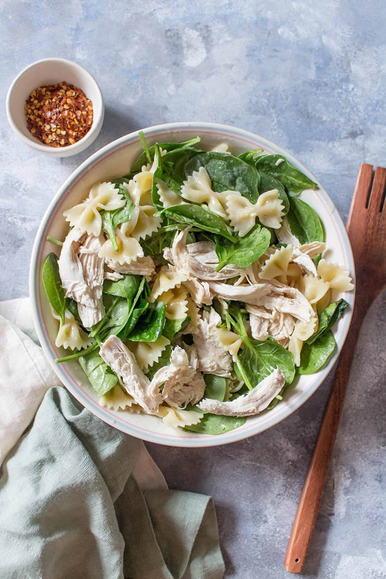 Cold spinach pasta salad with chicken in a white serving bowl by Carmy