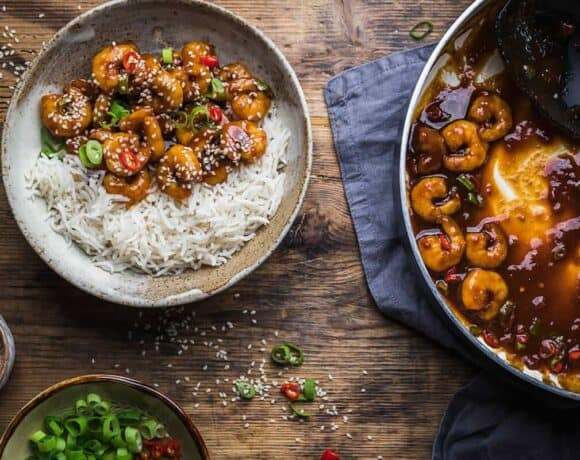 Chinese prawns recipe in a bowl with rice near pan with prawns and sauce