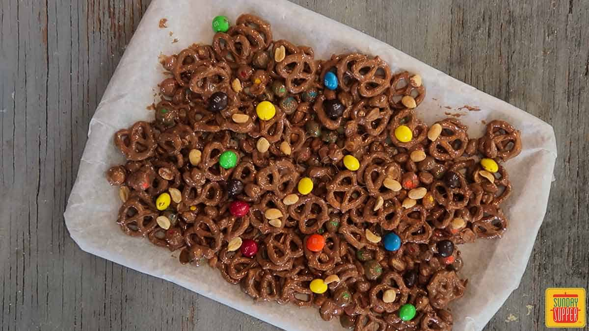 Peanut butter pretzel snack mix spread out on a parchment paper-lined baking sheet