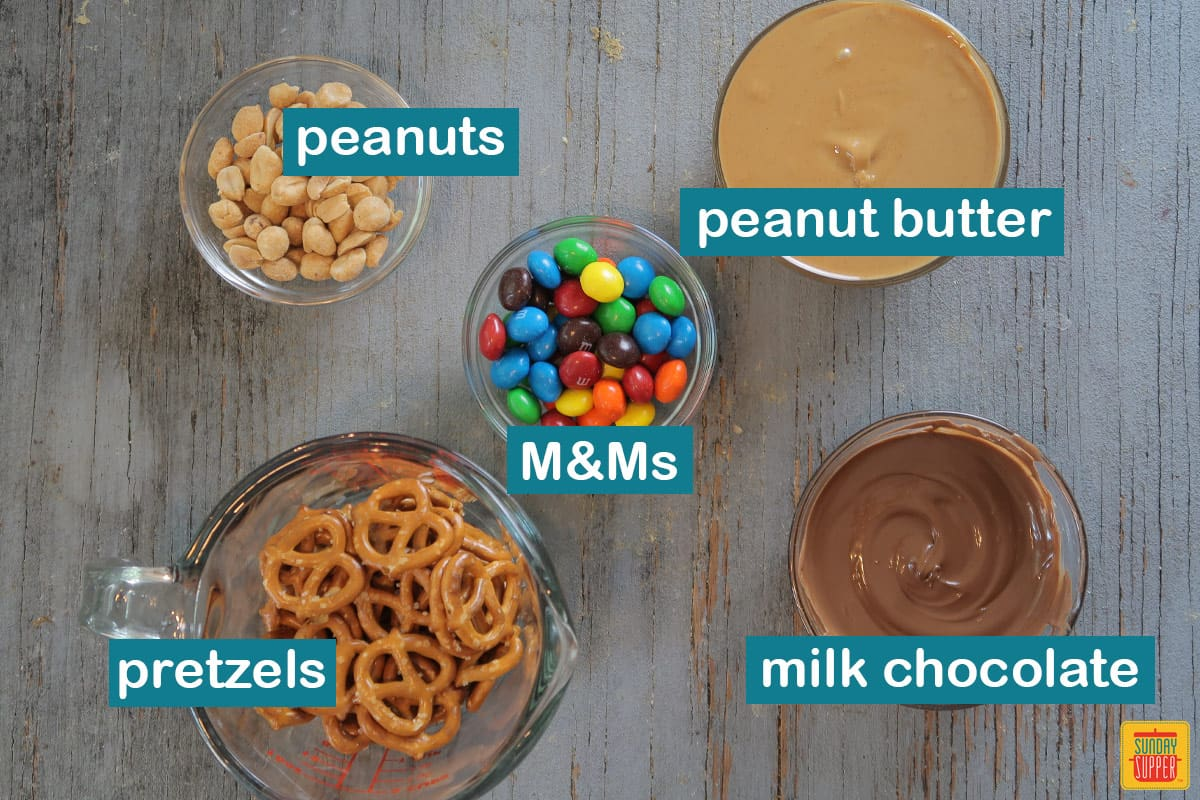 Ingredients for chocolate peanut butter pretzel snack mix labeled on the table