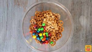 Peanuts, pretzels, and M&Ms in a glass bowl