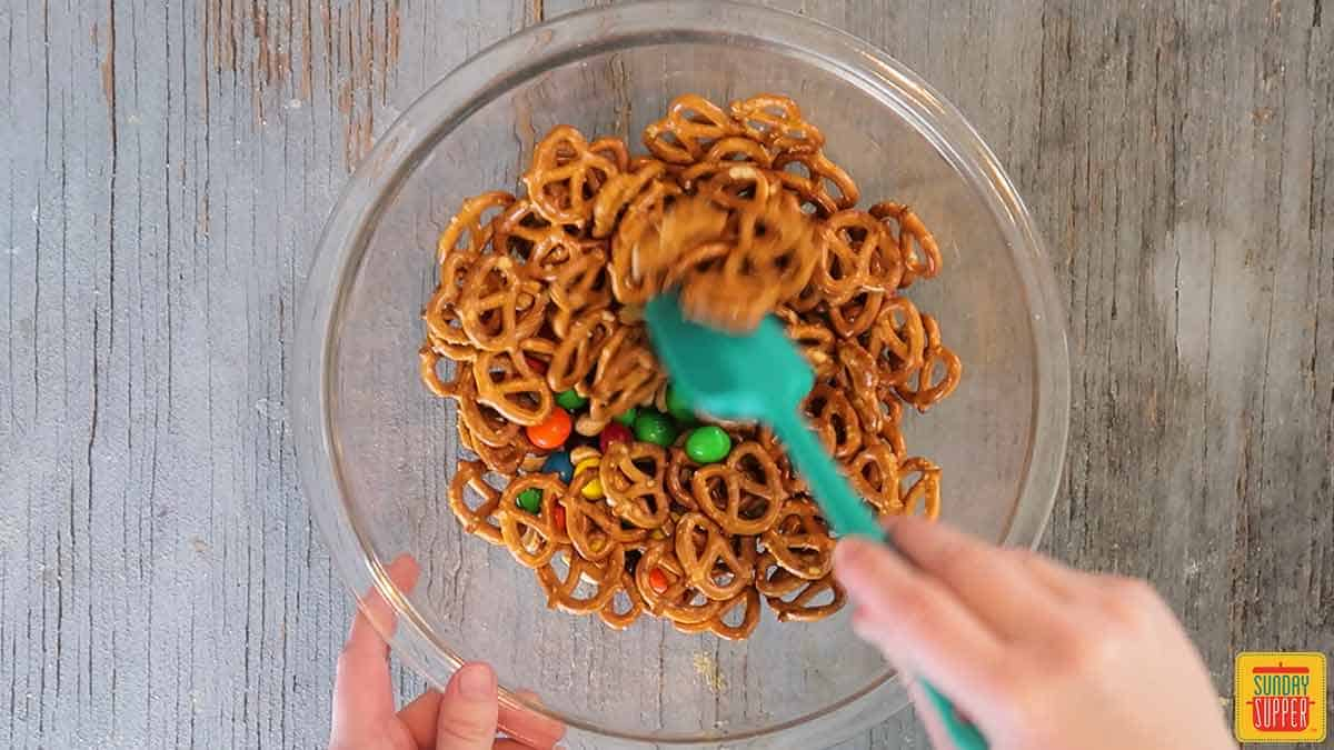 Mixing together the pretzels, peanuts, and m&ms with a small rubber spatula