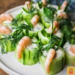 Cucumber canapes with shrimp on a white plate with fresh herb topping