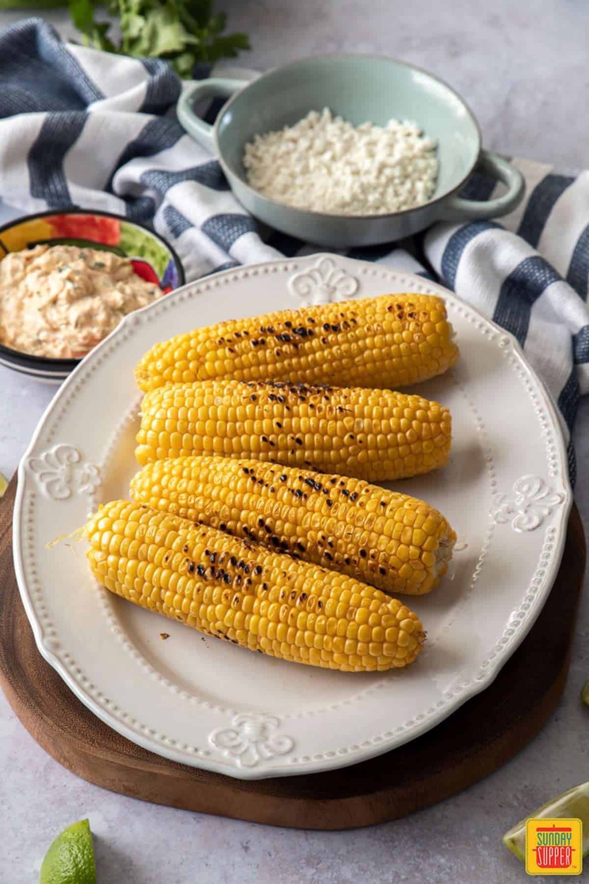 Grilled corn on a white platter for elotes Mexicanos