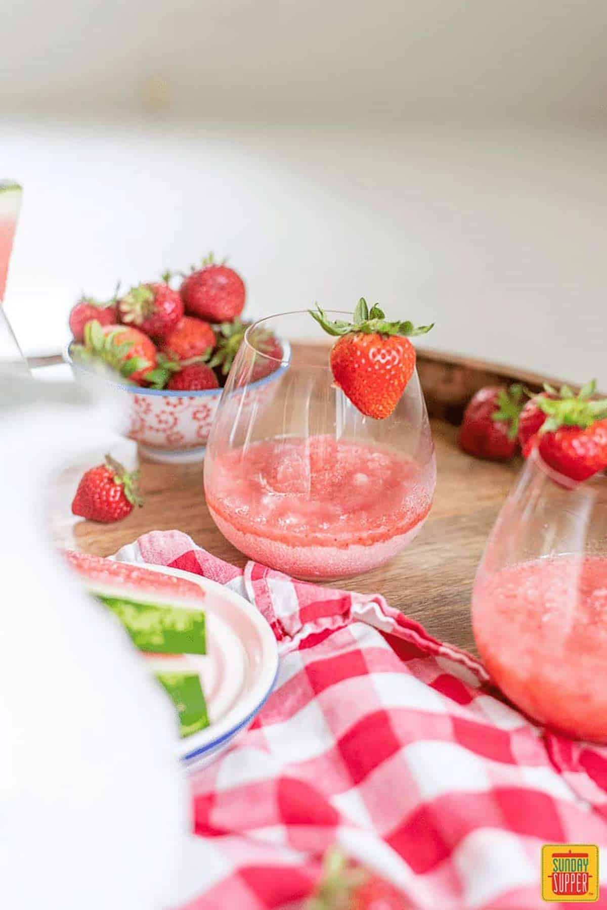 white pitcher near frose recipe in glasses with fresh strawberries