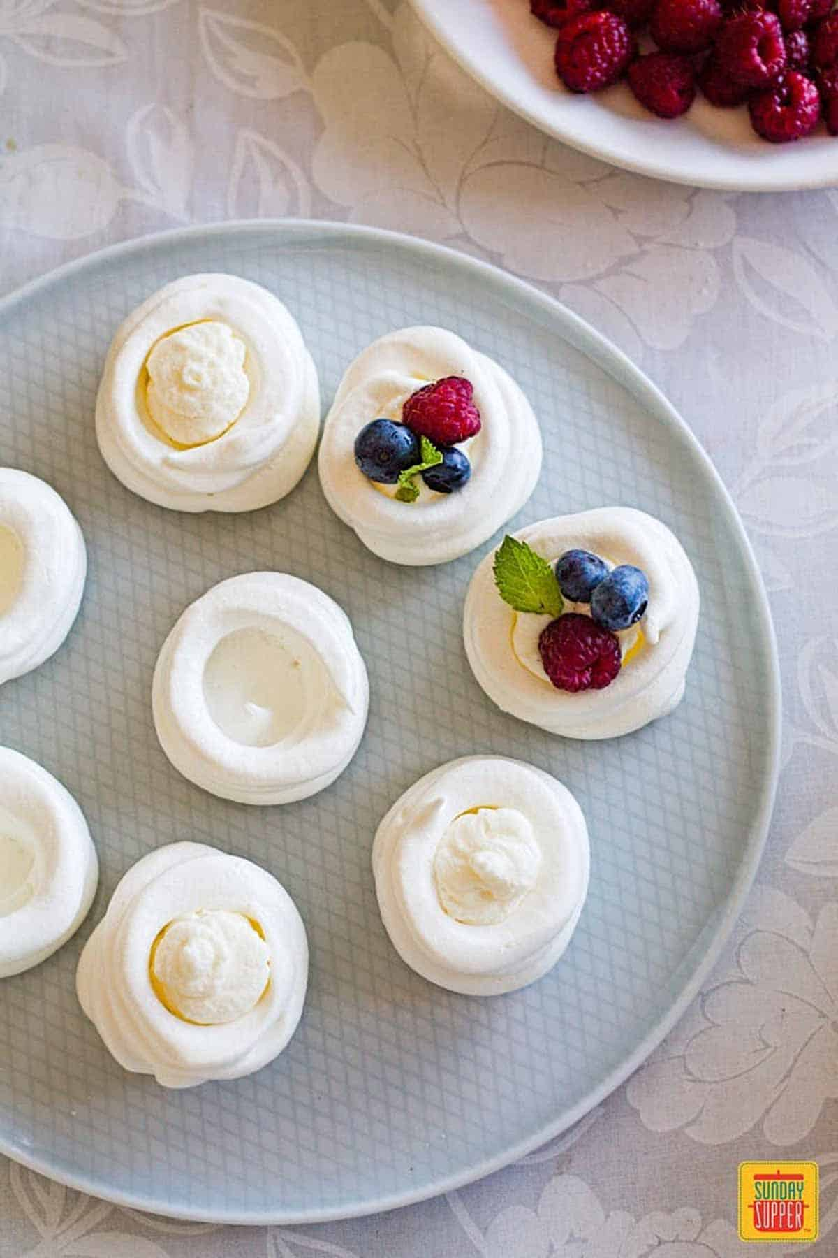 Filling piped into mini pavlovas on a light blue plate