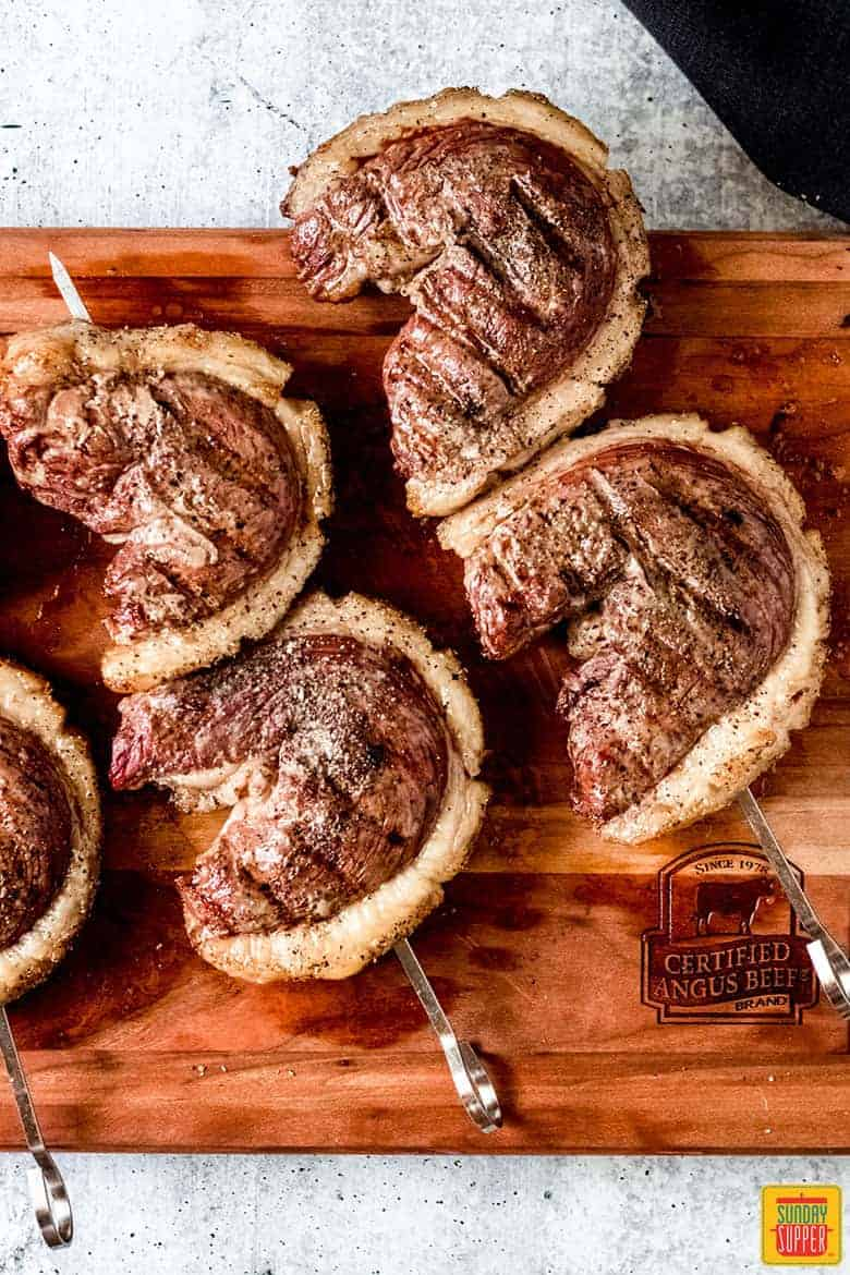 Four Picanha Steaks on skewers on a cutting board