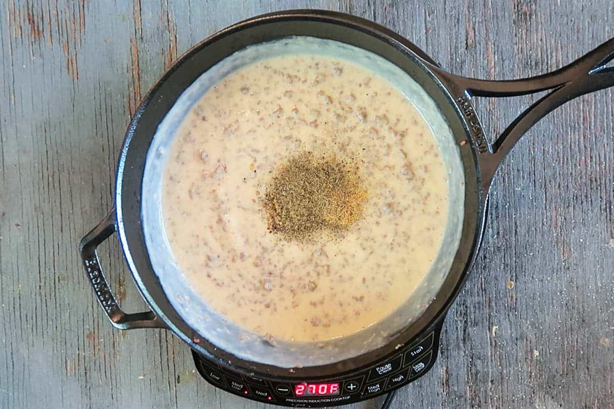 Adding pepper to sausage gravy in skillet