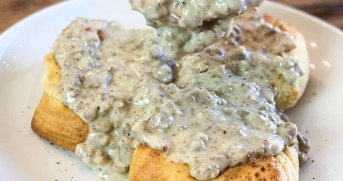 Pouring sausage gravy recipe on three fluffy biscuits