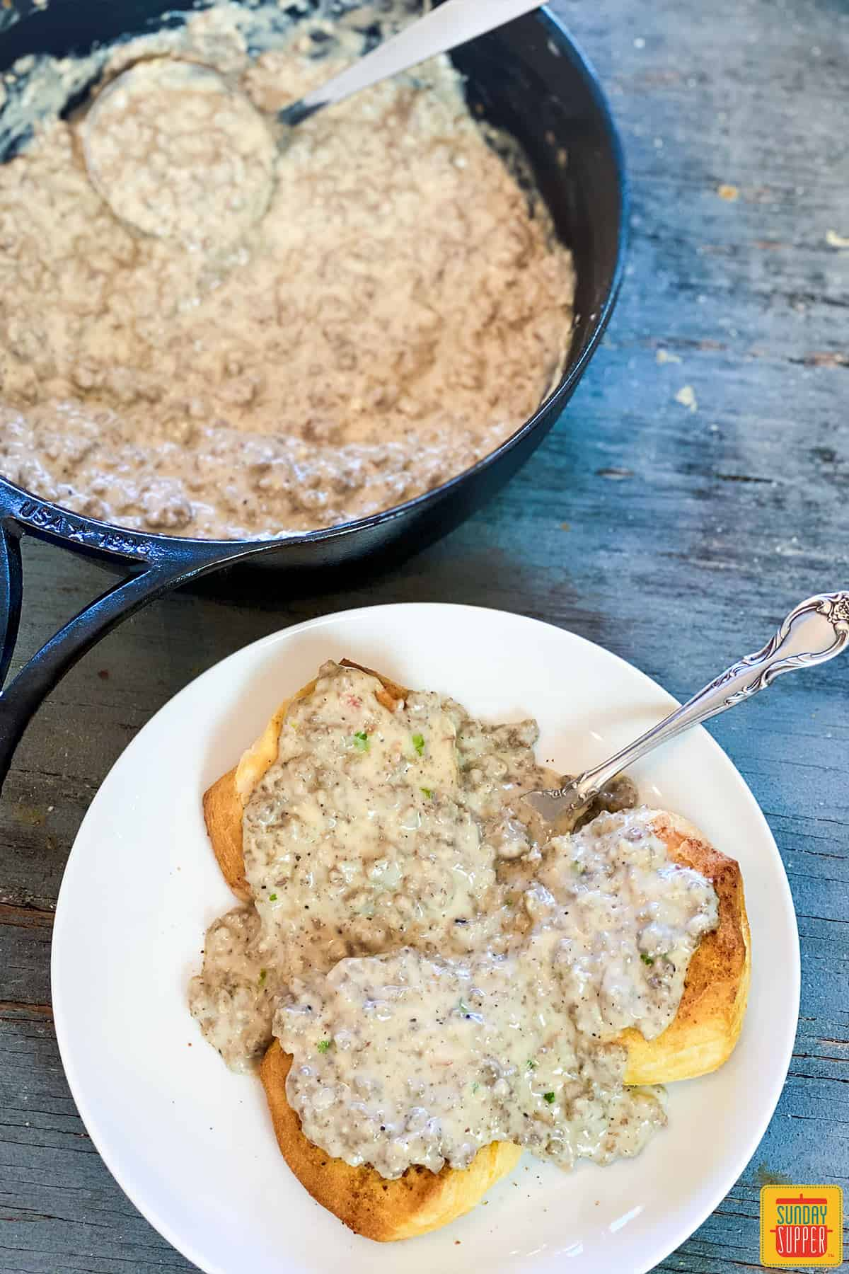 Sausage gravy biscuits on a white plate next to a skillet of sausage gravy