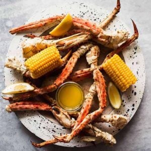 Steamed crab legs on a speckled plate with a glass dish of melted butter and two corn on the cob halves
