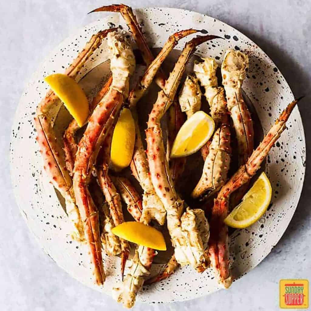 Boiled crab legs on a speckled white plate with lemon wedges
