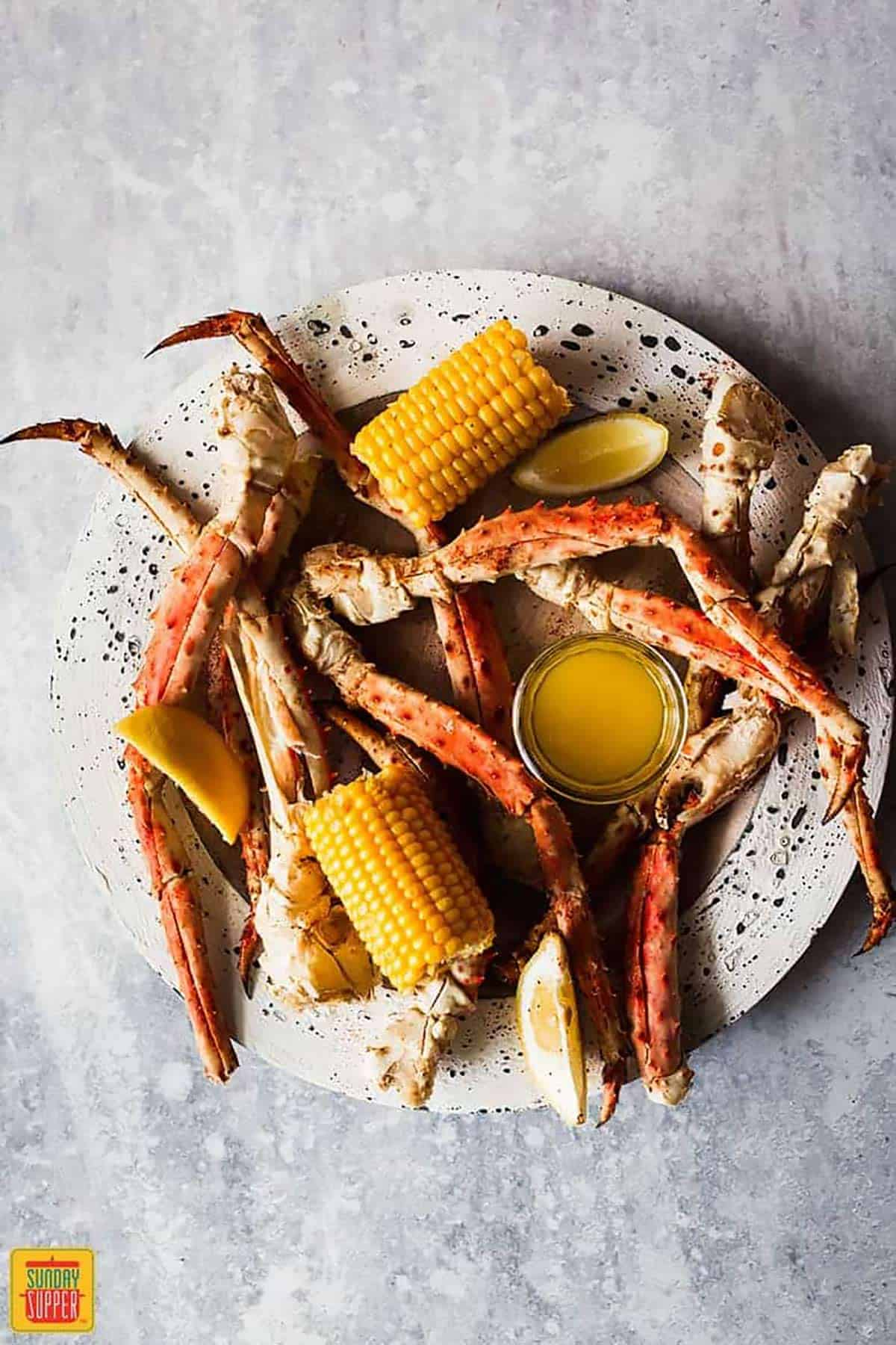 Steamed crab legs on a speckled plate with corn on the cob halves and a small dish of garlic butter sauce