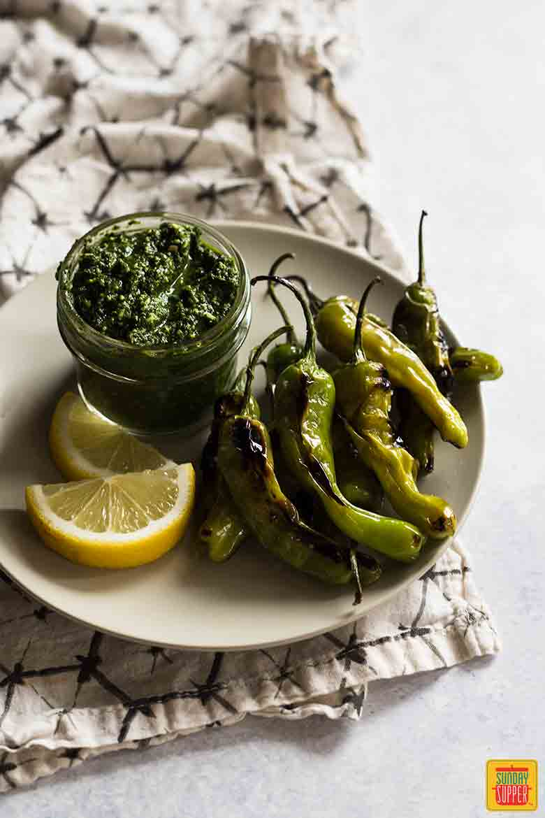 Blistered Shishito Peppers on a white plate with citrus pesto dip in a glass jar and lemon slices